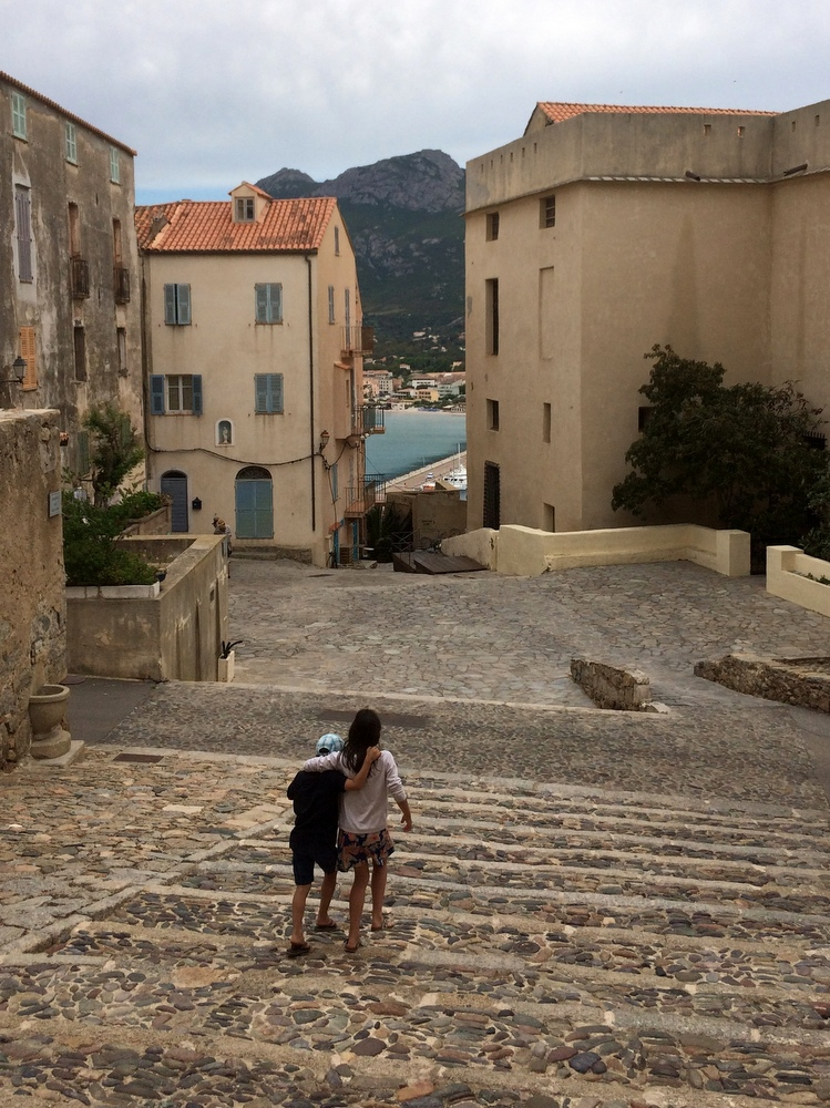 Brother and sister at Calvi's citadell walking down stairs arm in arm.